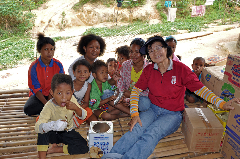 Auntie Rose giving biscuit to orang asli children