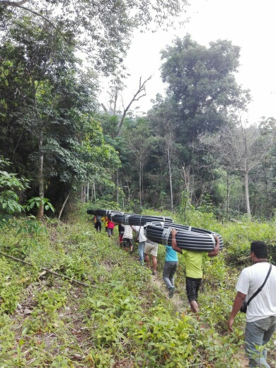 Kg Sinju villagers and SOA bringing pipes into hills for water source