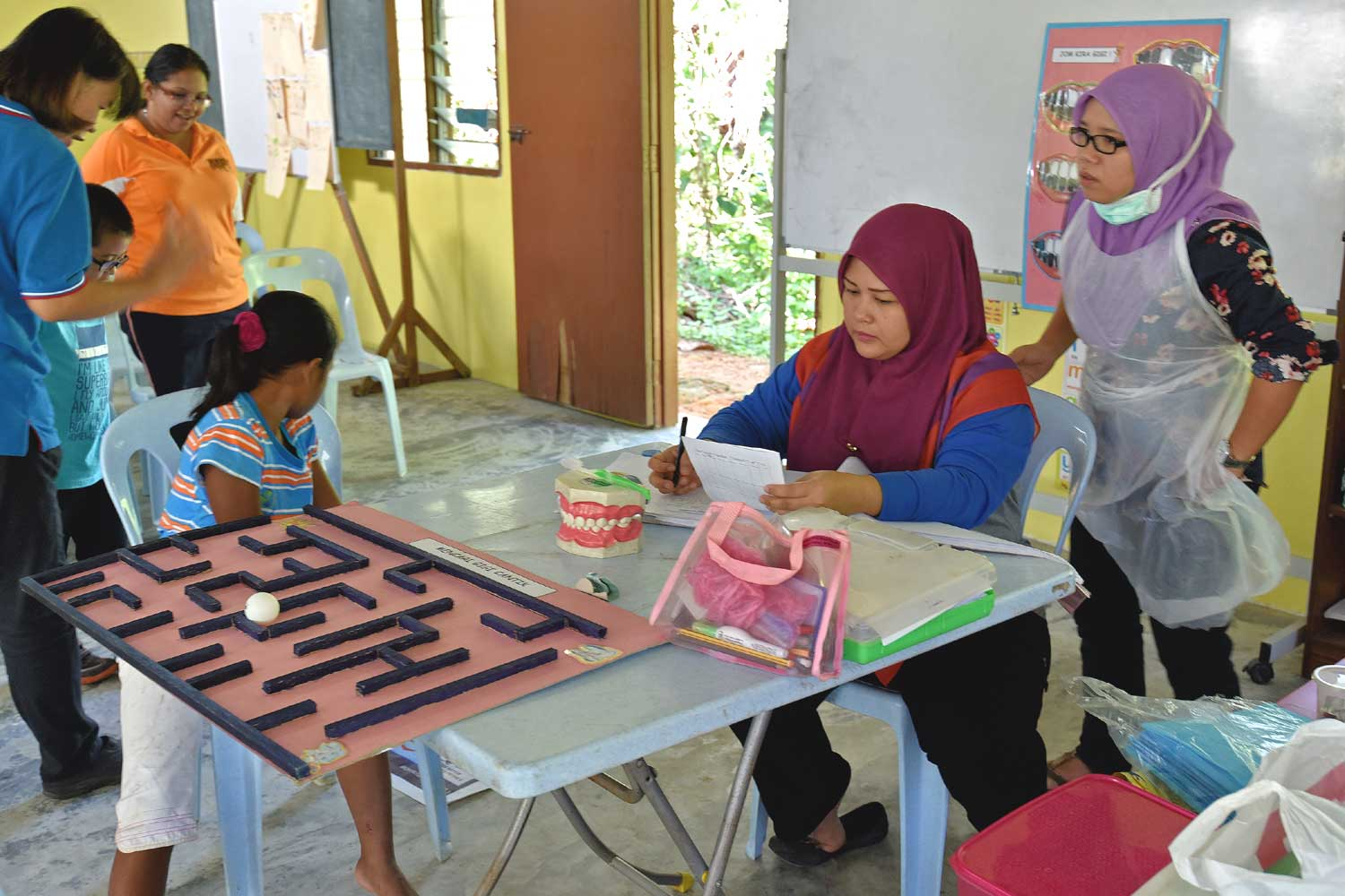 Nurses from Kuala Kangsar dental team with board game on oral health